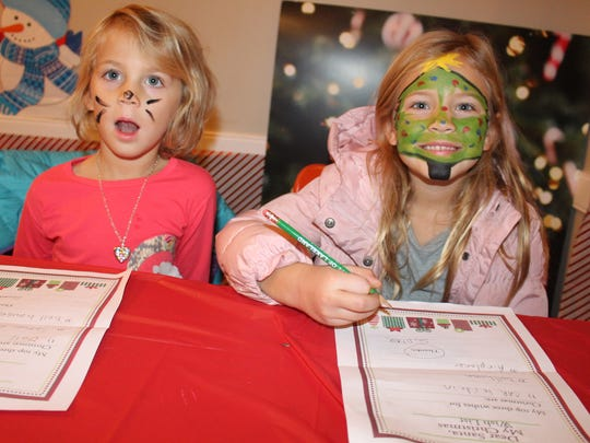 Sisters Savannah Scholten (left), 4, and Sophie Scholten, 6, fill out Christmas wish lists at one of the craft tables before seeing Santa.