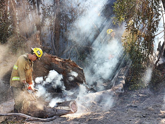 Ventura County and Santa Paula fire department crew members work Thursday morning on extinguishing hot spots off  South Mountain Road.