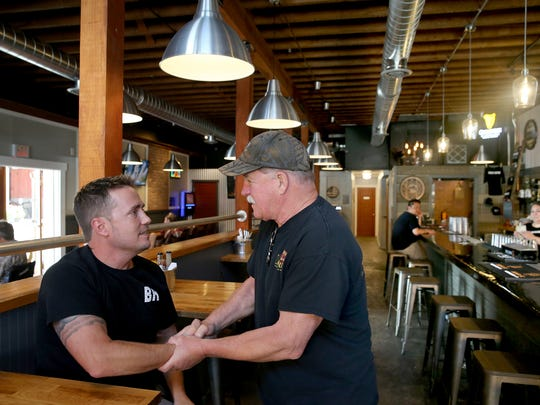 Kurt Craig, left, owner of Brick House 714 Bar & Grill in downtown Port Orchard, shakes hands with family friend Tom Davis of Hoodsport. Craig, who was raised in Port Orchard, said tried to maintain some of the building's history while renovating the bar that previously was known as MoonDogs Too and the Port Orchard Tavern.