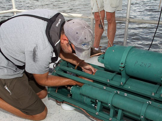 IRLON Technical Coordinator Jon Richardson makes the final connection with the water quality sensors before they are deployed.