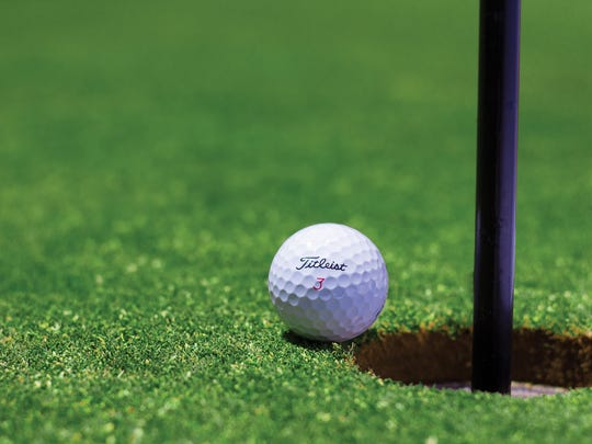 Golf ball and cup file photo.