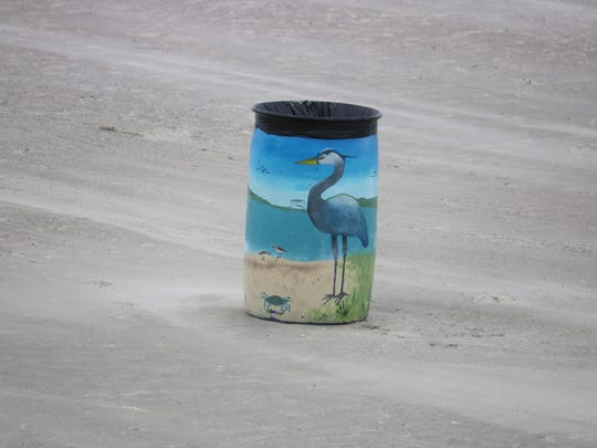 A painted trash can on Galveston Beach is appealing to the eye while chasing away the Litter Bug.