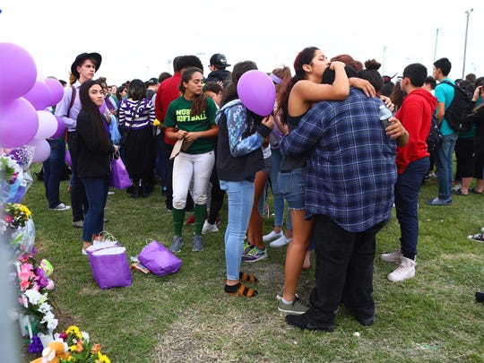 Mourners console one another Wednesday, March 28, 2018, during a vigil outside King High School for Rai-ane Garza, 16, who was killed by a hit-and-run driver Tuesday, March 27, 2018, just off campus.