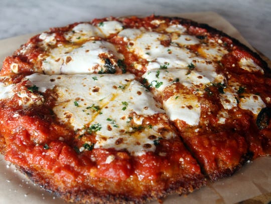 Chicken parmigiana takes the shape of a pizza at Tre