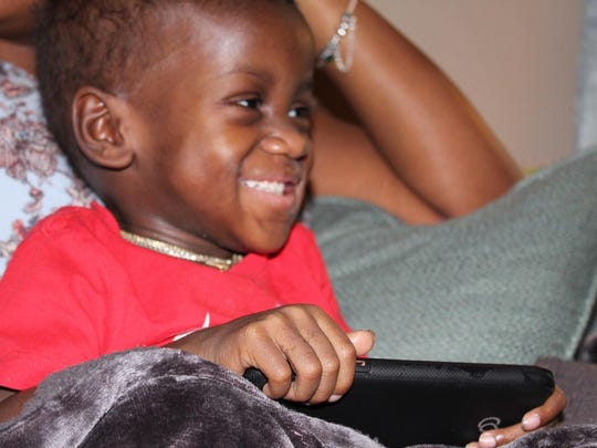 Julius smiles as he sits in his mom's lap.