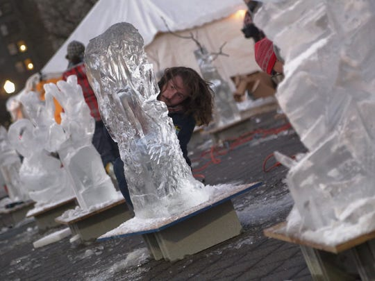 Nick Katsavrias, 21, of Detroit is a student at the College of Creative Studies and sculpts ice as a part of the Ice scrapper challenge in front of the Detroit Institute of Arts museum during Noel Night in Detroit on Saturday.