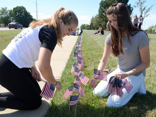 Northville High School students Autumn Gesierich, left, and Meghan Evans help to plant some of the thousands of American flags in front of the school on Sept. 10 for its 9-11 Never Forget project. The flag-planting was to memorialize those Americans who lost their lives in the Sept. 11 attacks of 2001.