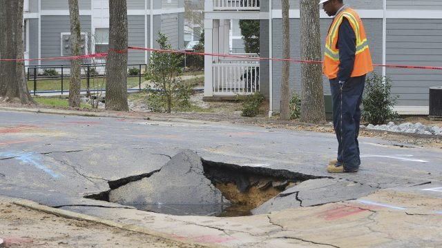 An Orange Sewer and Water Authority employee look at the water break damage in Chapel Hill, Friday, Feb. 3, 2017, in N.C., officials in Chapel Hill are asking everybody to stop using water after the water main break and a low tank levels. Bottled water is being rushed to student dorms at North Carolina's flagship public university and nearby nursing homes after a series of malfunctions shut down the municipal water system. Restaurants, schools in Chapel Hill and Carrboro and the University of North Carolina at Chapel Hill closed Friday after a water treatment plant was shut down by a miscue in chemical treatment and a water main broke.
