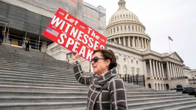 Laura Albinson of Pasadena, Md., displays a message for members of the House as they leave the Capitol in Washington, on Jan. 10. House Speaker Nancy Pelosi said Friday the House will take steps this week to send articles of impeachment to the Senate for President Donald Trump's Senate trial.