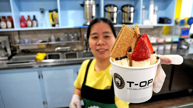 T-Op Cold Grill Ice Cream Manager Qui Chen shows off the popular cheesecake flavor ice cream, topped with strawberry, graham cracker and chocolate chips.