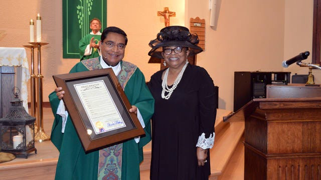 Columbia Vice Mayor Christa S. Martin presents the city proclamation to Father Davis.