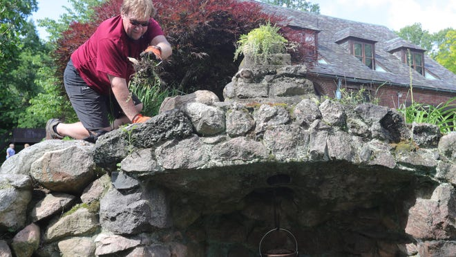 Volunteer Bob Gless of New Franklin clears weeds Thursday from the grotto area behind the Tudor House in New Franklin.