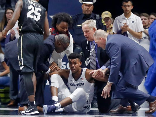 Xavier's Paul Scruggs, center, is helped to his feet after an apparent injury in the second half of an NCAA college basketball game against Colorado, Saturday, Dec. 9, 2017, in Cincinnati. (AP Photo/John Minchillo)