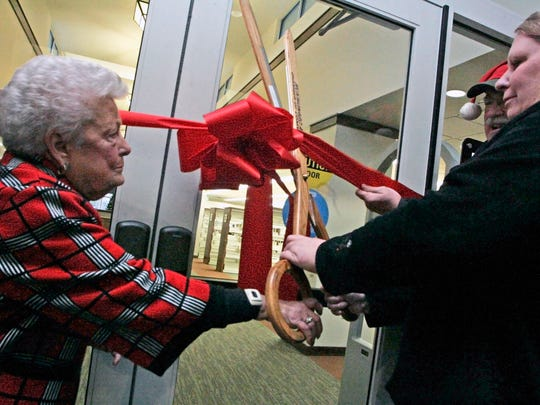 Lorraine McAdams (left) gets a hand from Mukwonago Library Board President Suzanne Ciechanowski and Mukwonago Village President Fred Winchowky during a ribbon-cutting ceremony in December 2011 to unveil the new Mukwonago Community Library. The village borrowed $4.55 million in 2010 to fund the library's expansion.