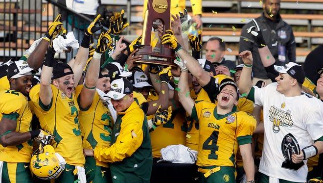 FILE ? In this Jan. 4, 2014 file photo, North Dakota State players celebrate with the trophy after beating Towson 35-7 in the FCS championship NCAA college football game in Frisco, Texas. The poll of league coaches, media and sports information directors released Tuesday, July 29, 2014, has NDSU picked to win the Missouri Valley Football Conference title this season. South Dakota State is picked to finish second in the conference. (AP Photo/Tony Gutierrez, File)