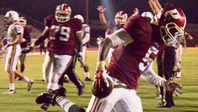 Pineville junior Jarious Green (5) celebrates after scoring a 12-yard touchdown against Marksville in the Rebels' 24-8 win last week.