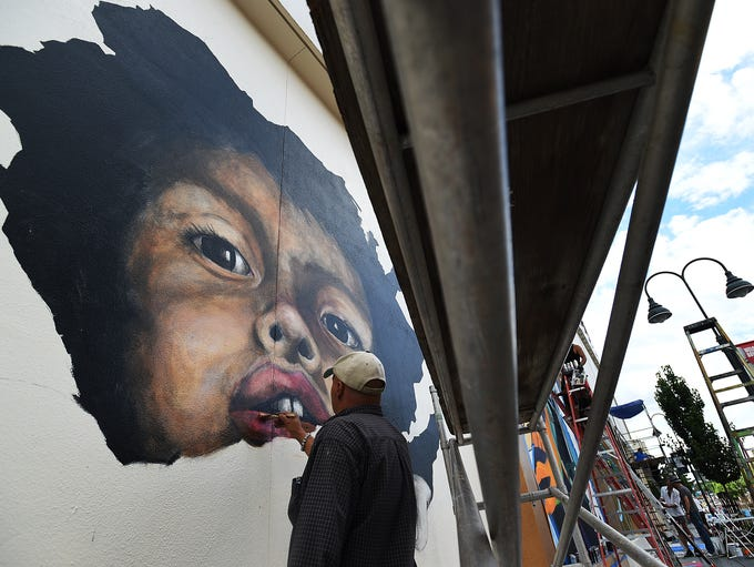 Artist Stephane Cellier works on painting of his son