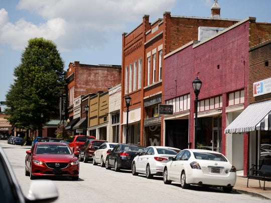 A motorist drives down Trade Street in downtown Greer