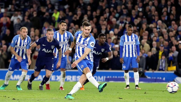 Brighton's Pascal Gross scores his side's first goal of the game from the penalty spot during the English Premier League soccer match between Brighton and Tottenham Hotspur, at the AMEX Stadium, in Brighton, England, Tuesday April 17, 2018. (Gareth Fuller/PA via AP)