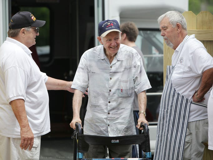 Springfield Elks Lodge members Jay Dolis, left, and Gary Comer, right, greet a veteran arriving at a cookout for veterans from the Mt. Vernon Veterans Home on Wednesday, June 11, 2014.