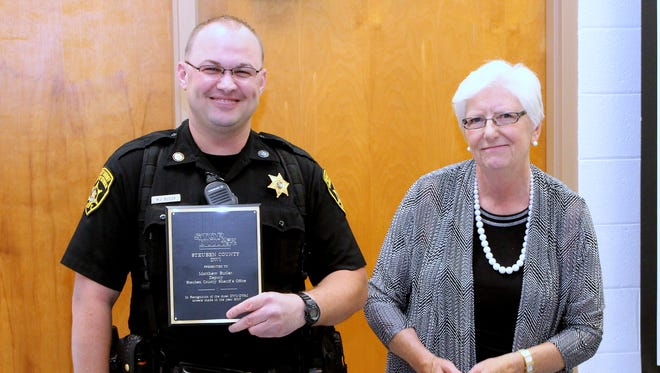 Steuben County sheriff's deputy Matthew Butler accepts the 2017 county STOP-DWI Officer of the Year award from county legislature Vice Chair Carol Ferratella.