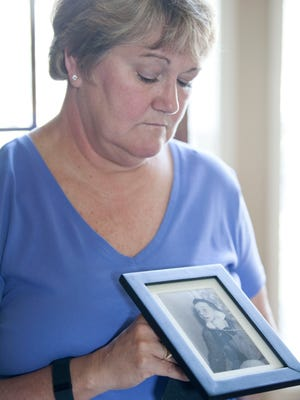 Cindy Harbin holds a photograph of her father, Karl Dowd.