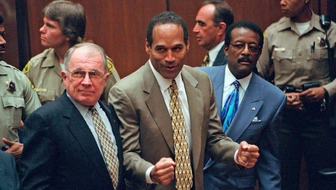 On October 3, 1995, O.J. Simpson, center, reacted as he was found not guilty of murdering his ex-wife Nicole Brown and her friend Ron Goldman. Members of his defense team, F. Lee Bailey, left, and Johnnie Cochran Jr., right, looked on, in court in Los Angeles.