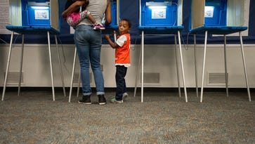 Gavin Edwards, 5, waits patiently as his great-aunt, Lorrie Witherspoon, fills out her ballot at the Durham County Main Library in Durham, N.C., on March 15, 2016.