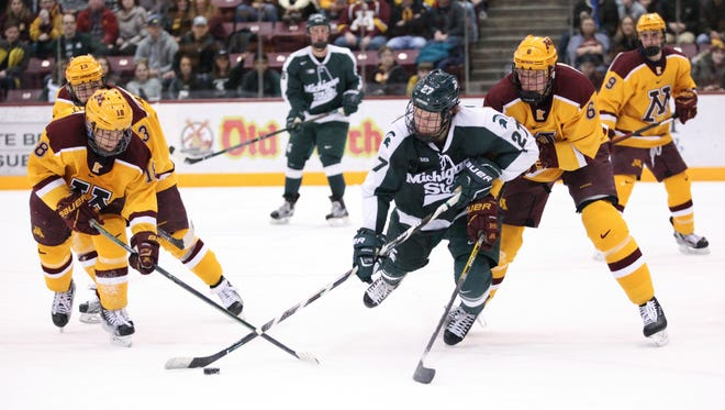 Minnesota's Leon Bristedt and Michigan State's Mason Appleton chase the puck in the second period at Mariucci Arena in Minneapolis on March 11, 2017.
