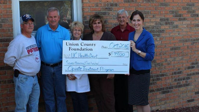 Opiate program founders Jeff Mathews, left, and Alvin Day, clinic nurse practitioner Vicky Wysong, county health nurse Kim Klein, Union County Foundation officer Dic Worcester and foundation executive director Danka Klein pose with a check for the drug treatment program.