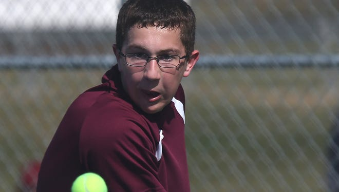 Dowling Catholic sophomore Jarrett Benson focuses on the ball before hitting it back to Linn-Mar's Brady Anderson, the defending state Class 2-A champion, in their tennis match at Dowling Catholic High School on Saturday.