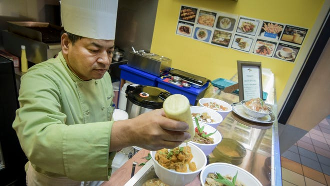 In this September 29, 2015 file photo, Chef Kotwal Singh garnishes a bowl of pumpkin curry, made from local pumpkin, at Singh's Cafe in the Micronesia Mall food court. Singh assures customers his food stall will continue to meet sanitation standards after it was closed from a public health inspection and reopened after passing inspection.
