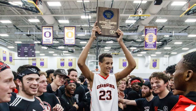 Sussex Hamilton freshman Patrick Baldwin Jr. hoists the championship plaque after Hamilton defeated Kettle Moraine 63-46 in the WIAA Division 1 Sectional final at Oconomowoc on Saturday, March 10.