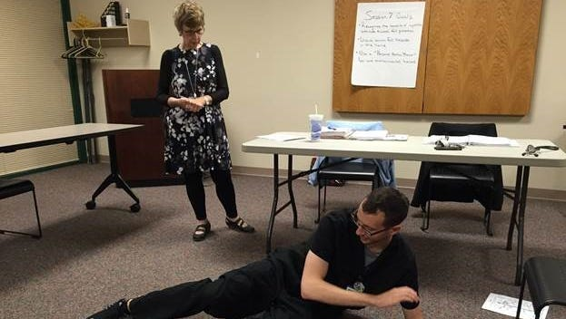 """Reda Willis, advanced clinical nurse, trauma services, WellSpan York Hospital, standing, and Shane Pirl, exercise physiologist, cardiac services, WellSpan York Hospital, explain how participants can safely recover from a fall during a """"A Matter of Balance"""" class held at WellSpan's Apple Hill Medical Center earlier this month."""