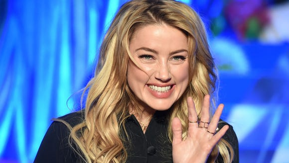 Amber Heard gives a wave, Monday, in Tokyo, at the
