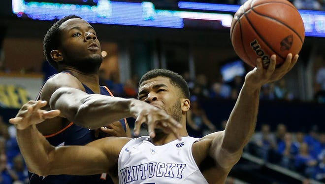 Kentucky guard Andrew Harrison (5) drives on Auburn center Trayvon Reed (4) during the second half of an NCAA college basketball game in the semifinal round of the Southeastern Conference tournament, Saturday, March 14, 2015, in Nashville, Tenn. (AP Photo/Steve Helber)