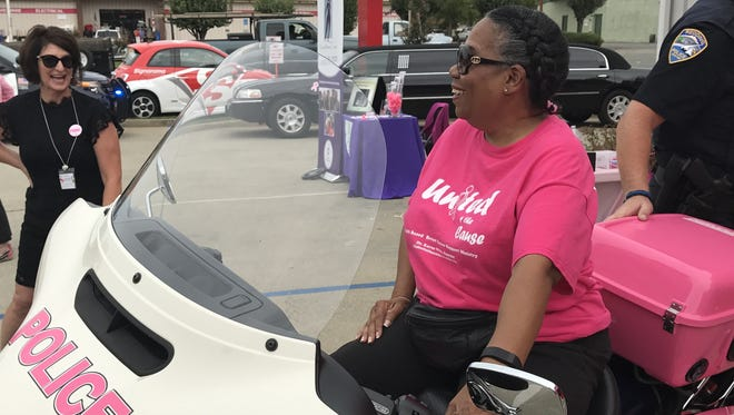 Jackie Morganfield of cancer support group United4theCause tries out the Redding Police Department's pink motorcycle Friday at Signarama. The department turned two vehicles pink to raise awareness about breast cancer.