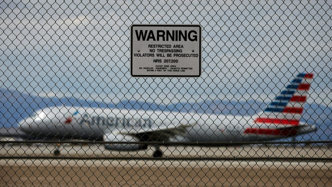 In this May 17, 2016, file photo, a sign warns against trespassing as a plane lands at McCarran International Airport in Las Vegas.