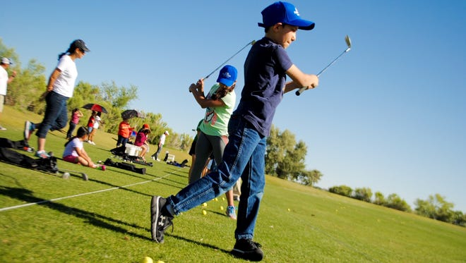 Alex Zander-Garcia practices his swing with a set of new golf clubs Saturday, while participating in the Clubs for Kids program.