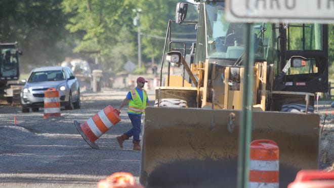 A Dan's Excavating employee moves traffic cones before leveling the gravel with a bulldozer on Hacker Road near Highland Road at the border of Oceola and Hartland townships.