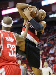 Portland Trail Blazers' Gerald Henderson (9) grabs a rebound from Houston Rockets' Corey Brewer (33) in the second half of an NBA basketball game Saturday, Feb. 6, 2016, in Houston. Portland won 96-79. (AP Photo/Pat Sullivan)