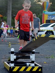 Four-year-old Cole Webster walks the plank on the obstacle course at the National Night Out event in Fanwood on Tuesday, Aug. 4.