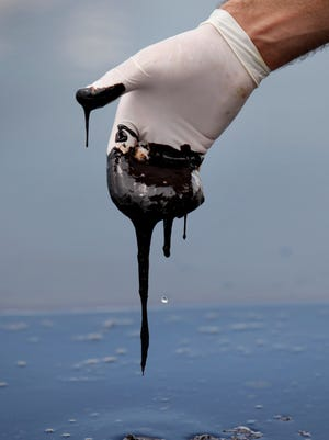A member of Louisiana Gov. Bobby Jindal's staff reaches into thick oil on the surface of the northern regions of Barataria Bay in Plaquemines Parish, La., June 15, 2010. BP estimates it has already piled up $42 billion in costs related to the oil spill and is pushing for an unspecified lighter penalty.