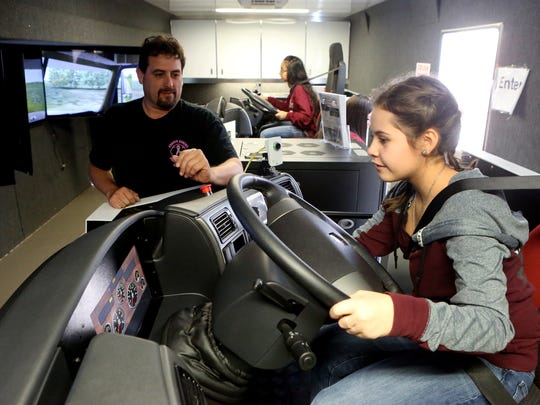 Emma Perez prepares to drive a simulated semi truck with the help of Instructor of Transportation Training Service Edward Saenz from Del Mar College during the Discover Your Direction Conference on Thursday, Feb. 9, 2017, at the Education Service Center Region 2 in Corpus Christi.