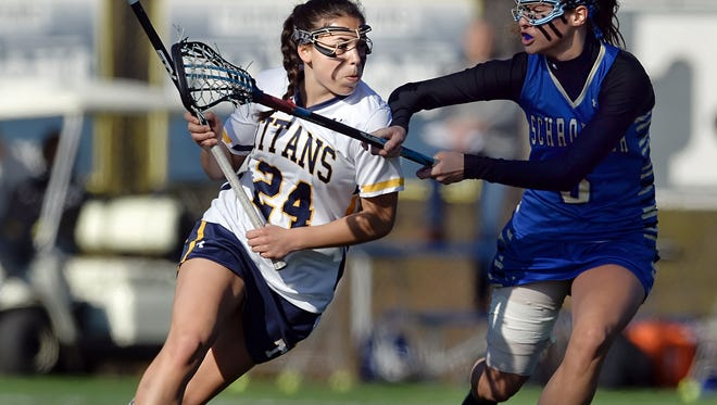 Webster Thomas' Emily Resnick, left, carries the ball past Webster Schroeder's Casey Roux during regular season game played at Webster Thomas High School on Saturday, April 25, 2015. Webster Thomas beat Webster Schroeder in overtime, 10-9.