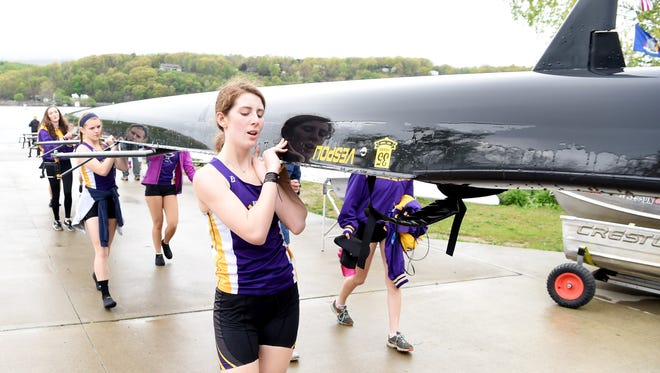 Madison Lortie and the Rhinebeck High School girls varsity 8 boat crew carry their boat back into its bay at the Hudson River Rowing Association during the Triangulars Regatta in Poughkeepsie on May 7.