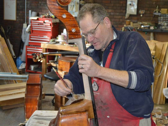 Bassist/luthier Chris Roberts stains a new neck on a repaired bass at Cincinnati Bass Cellar.