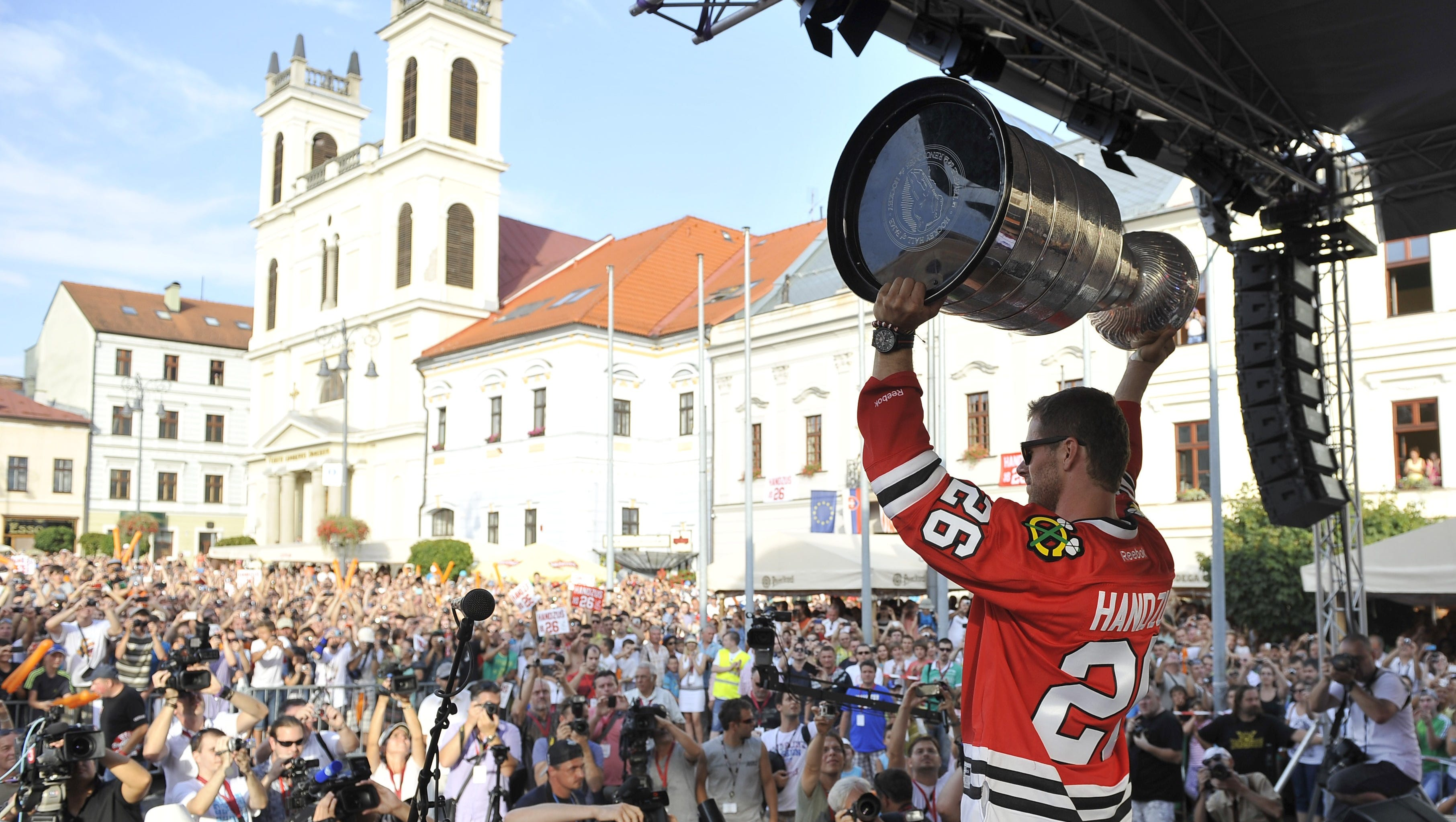 Michal Handzus lifts the Stanley Cup after arriving in the main square of Banska Bystrica, Slovakia. Reports says 10,000 people were in the crowd.