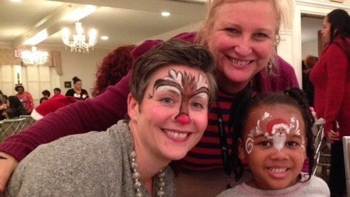 Blythe Spitsbergen, the new CARE House director, got into the spirit of the evening with her face painted like a deer. Her painted face was a delight to 4- year-old Lily Cottingham, with her Santa face. Early Head Start teacher Silvia Ibanes shares their delight at the CARE House Holiday Party at The Community House.