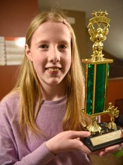 Lydia Johnson holds her first-place trophy from the